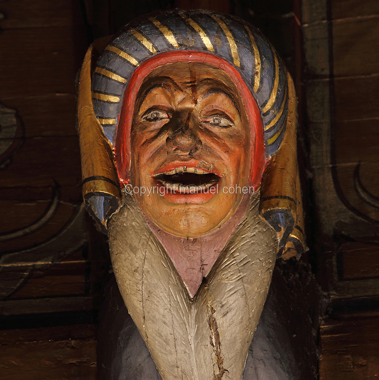 Carved and painted roof bracket with head of a laughing man wearing a traditional headdress, architectural detail of the painted wooden ceiling in the shape of a boat's hull, in the Salle des Povres or Room of the Poor, almost 50m long, in Les Hospices de Beaune, or Hotel-Dieu de Beaune, a charitable almshouse and hospital for the poor, built 1443-57 by Flemish architect Jacques Wiscrer, and founded by Nicolas Rolin, chancellor of Burgundy, and his wife Guigone de Salins, in Beaune, Cote d'Or, Burgundy, France. The hospital was run by the nuns of the order of Les Soeurs Hospitalieres de Beaune, and remained a hospital until the 1970s. The building now houses the Musee de l'Histoire de la Medecine, or Museum of the History of Medicine, and is listed as a historic monument. Picture by Manuel Cohen