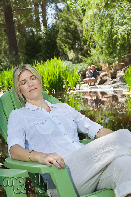 Mature woman resting in chair with man and son fishing in the background
