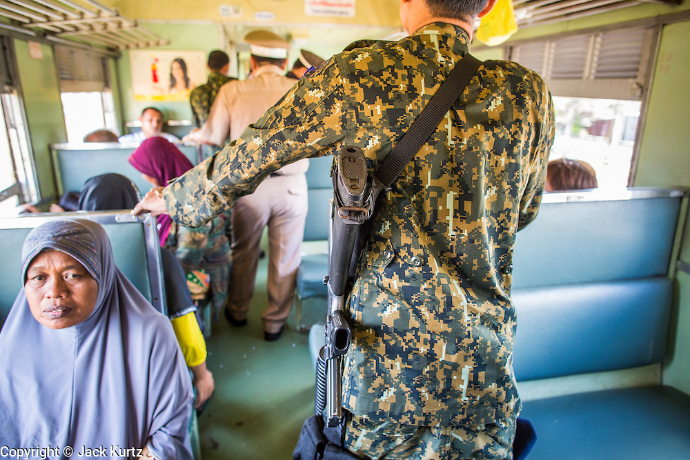 27 OCTOBER 2012 - SUNGAI KOLOK, NARATHIWAT, THAILAND:     Civil defense volunteers armed with M16 rifles escort a train conductor past Muslim passengers on a northbound train out of Sungai Kolok, Thailand. Sungai Kolok has been a center of extremist violence. Several car bombs have been detonated in the city, which is on the Malaysian border and very popular with Malaysian tourists. More than 5,000 people have been killed and over 9,000 hurt in more than 11,000 incidents, or about 3.5 a day, in Thailand's three southernmost provinces and four districts of Songkhla since the insurgent violence erupted in January 2004, according to Deep South Watch, an independent research organization that monitors violence in Thailand's deep south region that borders Malaysia.   PHOTO BY JACK KURTZ