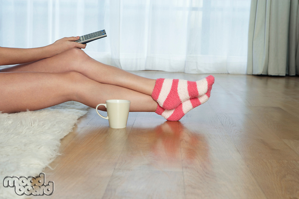 Low angle view of woman in stripey socks holding remote control