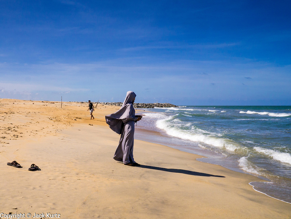 28 OCTOBER 2012 - SAI BURI, NARATHIWAT, THAILAND: A Muslim on deserted Wasukrit beach in Sai Buri, Thailand. Sai Buri, in Narathiwat province, Thailand, has been the scene of several bloody attacks in Thailand's long running Muslin insurgency. In September, 2012, a large car bomb was detonated in front of a Buddhist owned business in the village killing more than 9. In October, 2012, in a possible revenge attack, hand grenades were rolled into a crowd of Muslim diners, injuring nine. More than 5,000 people have been killed and over 9,000 hurt in more than 11,000 incidents, or about 3.5 a day, in Thailand's three southernmost provinces and four districts of Songkhla since the insurgent violence erupted in January 2004, according to Deep South Watch, an independent research organization that monitors violence in Thailand's deep south region that borders Malaysia.    PHOTO BY JACK KURTZ