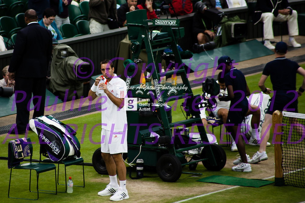 Victor Troicki glances at his team in the players box while taking a drink during the match at Wimbledon