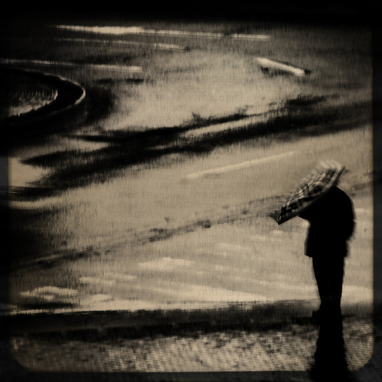A single figure standing alone with an umbrella