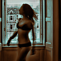 Young woman in underwear dancing in a dimly lit room