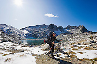 A woman wearing a backpack hiking through a high alpine landscape, Enchantment Lakes Wilderness Area, Washington Cascades, USA.