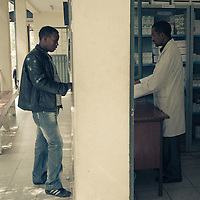 A patient and a pharmacist interact at the drugstore. The man was there to collect his HIV antiretrovirals. Addis Ababa, Ethiopia.