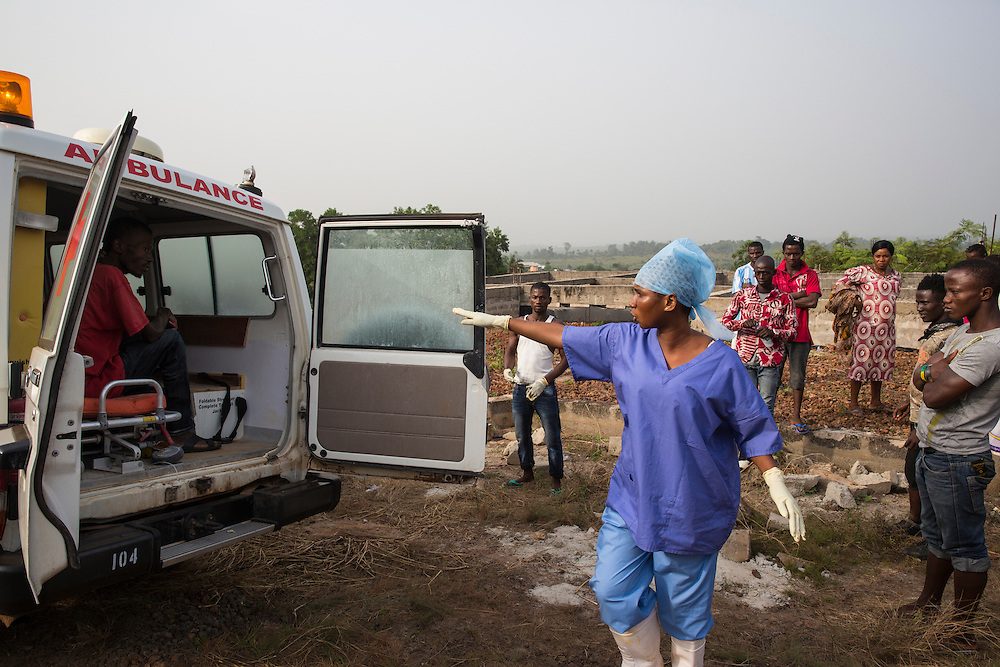 Ambulance being dispatched to westren area of Freetown, Sierra Leone to attend a suspected case of ebola. The nurse is seen here with the susptected case. Photo by UNMEER/Martine Perret. 15 December 2014
