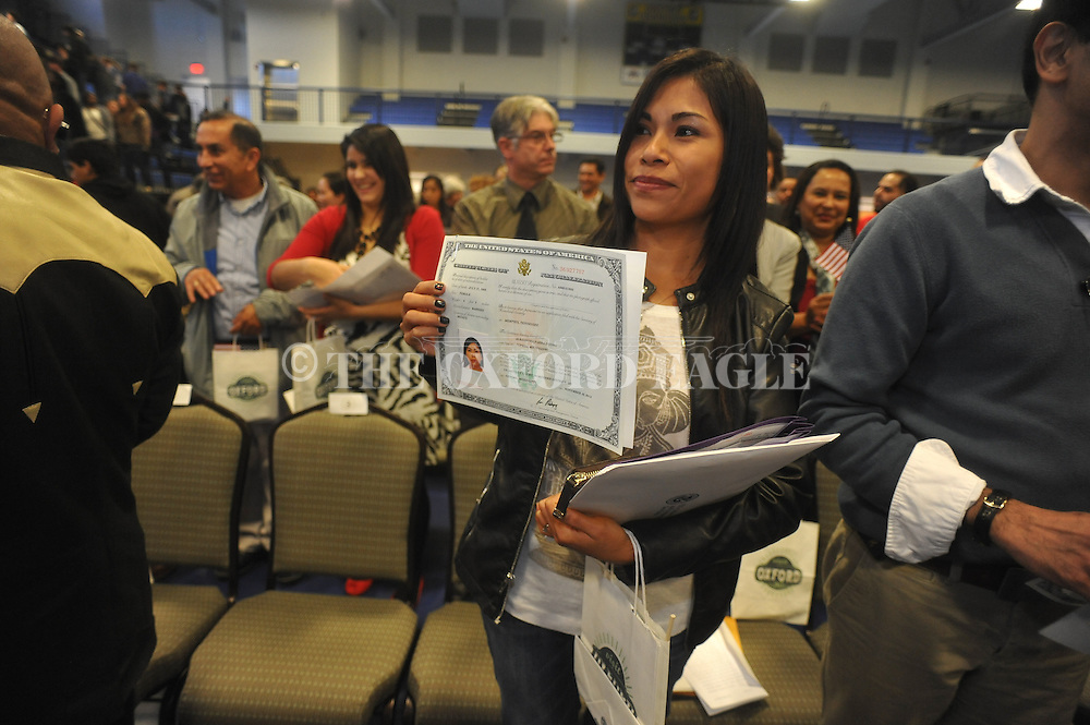 Alejandra Parra Duong holds her citizenship papers following a Naturalization Ceremony in U.S. District Court for the Northern District of Mississippi, at Oxford High School in Oxford, Miss. on Tuesday, November 18, 2014. The ceremony was the first the court has ever held at the school.
