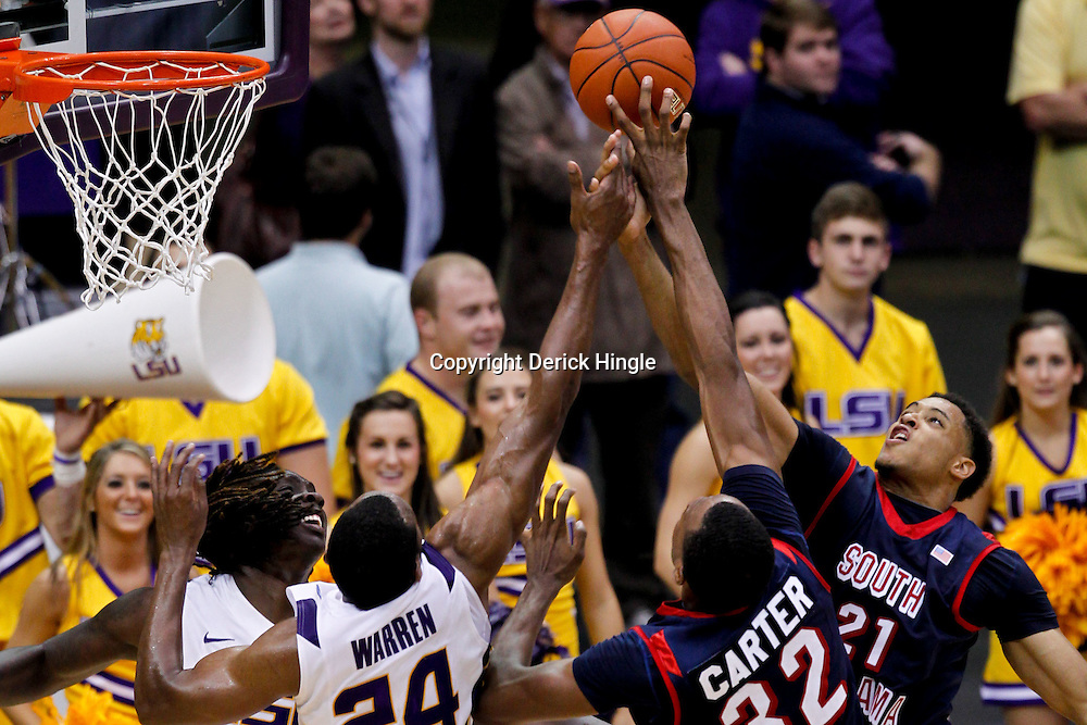 November 23, 2011; Baton Rouge, LA; LSU Tigers forward Johnny O'Bryant (2) and forward Storm Warren (24) jump for a rebound with South Alabama Jaguars forward Javier Carter (32) and center Augustine Rubit (21) during the second half of a game at the Pete Maravich Assembly Center. South Alabama defeated LSU in overtime 79-75. Mandatory Credit: Derick E. Hingle-US PRESSWIRE