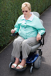 Woman wheelchair user travelling on the pavement,
