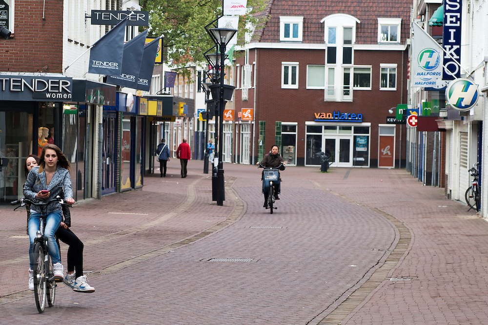 Fietsers rijden door het centrum van Zevenaar, een plaats in de streek De Liemers in het oosten van Nederland. <br /> <br /> Cyclists ride through the center of Zevenaar, a place in the region the Liemers in the east of the Netherlands.