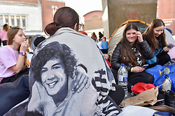 © Licensed to London News Pictures. 29/10/2017. London, UK.  A fan wears a blanket showing the face of singer, Harry Styles.  Fans queue up outside the Hammersmith Eventim Apollo in West London ahead of his first UK solo shows taking place on 29 and 30 October.  Many fans, eager to secure a space as close to the stage as possible have queued overnight, sleeping on the pavement in their sleeping bags or under duvets.  Fans immediately outside the entrance to the venue will be seeing the singer perform on the 29 October, whilst those under the nearby Hammersmith flyover (pictured) have arrived a day early with tickets for 30 October.  Photo credit: Stephen Chung/LNP