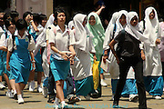 A group of students crosses a street after a day of classes in the Georgetown district of Penang, Malaysia.
