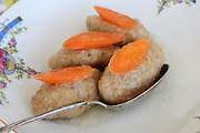 Gefilte fish with carrot. A traditional Askenazi Jewish festive dish of poached fish patties made from a mixture of ground deboned carp, traditionally eaten on the Jewish Rosh Hashana Feast and Passover Seder