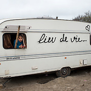 France, Calais. Refugee camp - the so-called Jungle. A young Iraqi Kurdish refugee girl in her family's  caravan which has 'lieu de vie' (living space) written on it so that it wouldn't be destroyed..