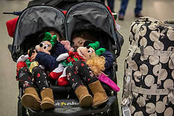© Licensed to London News Pictures. 20/12/2019. Florence and twin Fleur Freeman from Buckinghamshire have a sleep while waiting for their train to Disneyland Paris as the Christmas Getaway starts at St Pancras Station. Heavy rain today is causing chaos for the  thousands who are expected to travel for the festive period: Alex Lentati/LNP