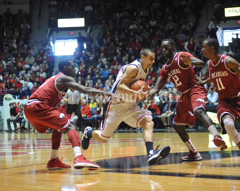 """Ole Miss' Marshall Henderson (22) vs. Arkansas' Fred Gulley (12) and Arkansas' B.J. Young (11) at the C.M. """"Tad"""" Smith Coliseum in Oxford, Miss. on Saturday, January 19, 2013. Mississippi won 76-64. (AP Photo/Oxford Eagle, Bruce Newman)"""