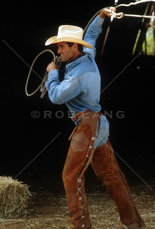 sexy cowboy in chaps working inside a barn