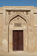 Carved entrance with wooden door at the Sheikh Salman bin Ahmed Al-Fateh Fort, or Riffa Fort, built in the 17th century and rebuilt as the ruling Al Khalifa family home in 1812, at Riffa, Bahrain. The fort is square with 2 circular and 2 rectangular towers at its corners, and 3 courtyards. It was restored in the 20th century and is now a tourist attraction. Picture by Manuel Cohen