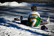 Young boy sits on the ice between makeshift hockey goal markers.