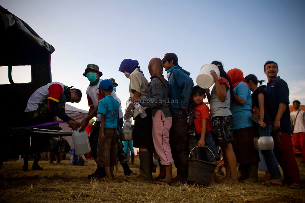 refugees whose homes were damaged by the earthquake in Pangalengan, West Java, Indonesia in line to get clean water.