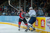 KELOWNA, CANADA - OCTOBER 11:  Tyson Baillie #24 of the Kelowna Rockets checks Kevin Wolf #3 of the Seattle Thunderbirds into the boards on October 11, 2013 at Prospera Place in Kelowna, British Columbia, Canada (Photo by Marissa Baecker/Shoot the Breeze) *** Local Caption ***