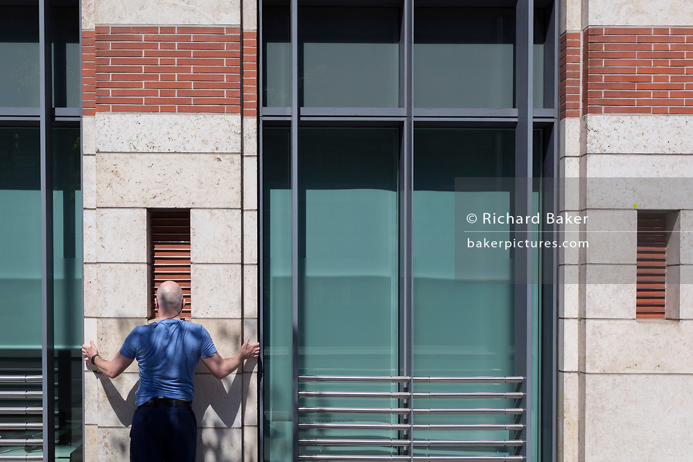 Having completed his urban run through the City of London the capital's financial capital, an office worker stretches against the exterior wall of his place of work, on 13th May, in London, England.