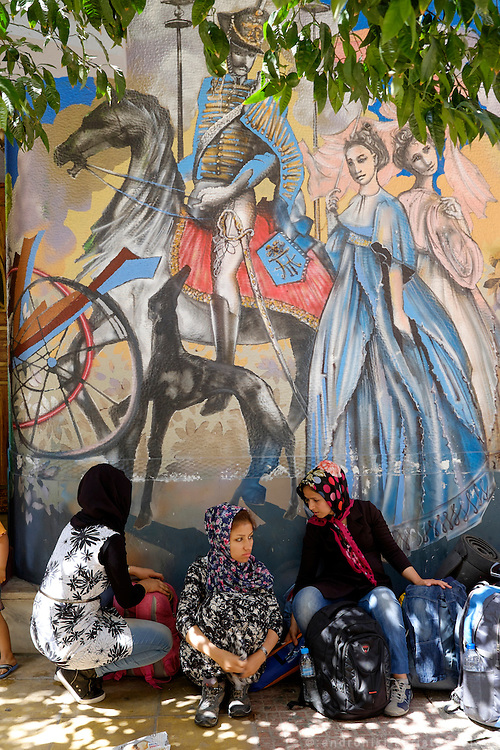 Afghani girls who just arrived in Victoria square in Athens, after spending the night at a hotel together with their families, in order to have a shower and recover from their trip till then. They temporarily settled in front of a building with farry-tale theme painted walls near the square.<br /> Victoria square in Athens is one of the main gathering places for refugees. They stay there until they can find a way to travel to Thessaloniki and to the northern border of Greece where they can cross on foot on their way to northern European countries.