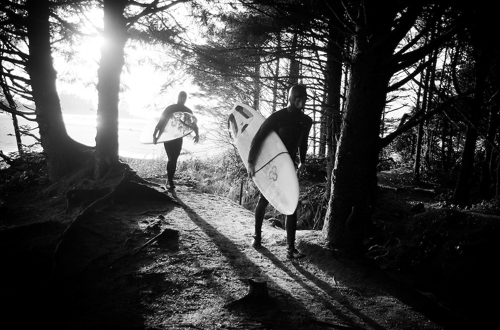 Surfers walk on a path that leads from Middle Chesterman Beach in Tofino, British Columbia to a parking area.