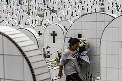 April 14, 2017 - Medan, North Sumatra, Indonesia - Indonesian women brought flowers to the grave pilgrimage to his family members during Good Friday at a Christian cemetery in Medan on April 14, 2017, Indonesia. As Christians mark Friday as the death, of the life after the third day, otherwise known holy week of Easter Sunday in celebration of the crucifixion and resurrection Jesus Christ, a as Muslim-dominated population country. Christians in Indonesia visited the grave of their families member  who believe in living with Jesus Christ. (Credit Image: © Ivan Damanik via ZUMA Wire)