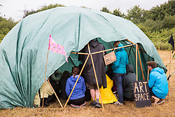Roydon, Essex, UK. 27 July, 2019. Activists listen to a talk at the Art Space at Reclaim The Power's Power Beyond Borders mass action camp.