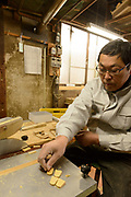 Masahara Nakajima, owner of Nakajima Seikichi Shoten, laying out semi-finished shogi playing pieces. Tendo, Yamagata Prefecture, Japan, February 19, 2018. The city of Tendo in Yamagata Prefecture is famous for its shogi (Japanese chess) playing pieces. Production started early in the 19th century and Tendo still produces over 95% of the Shogi pieces made in Japan.