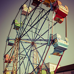Newport Beach Ferris Wheel in Balboa Fun Zone photo. Picture has a vintage style tone applied. The Ferris Wheel at the Balboa Fun Zone is a popular attraction in Orange County in Southern California.