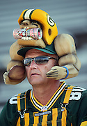 A Green Bay Packers fan wearing team colored head gear and apparel before the 2016 NFL Pro Football Hall of Fame preseason football game against the Indianapolis Colts on Sunday, Aug. 7, 2016 in Canton, Ohio. The game was canceled for player safety reasons due to the condition of the paint on the turf field. (©Paul Anthony Spinelli)