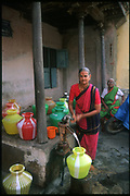 Women collecting water in colourful plastic water post. Chennai. Tamil Nadu.