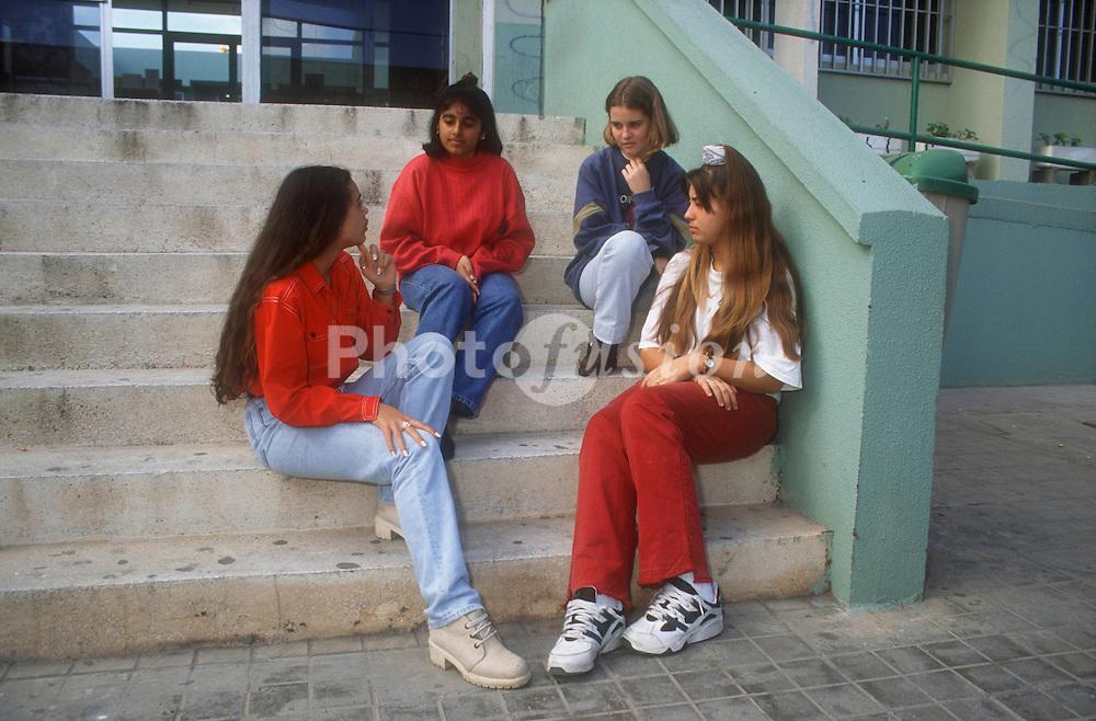 Group of teenage girls sitting on school steps talking,