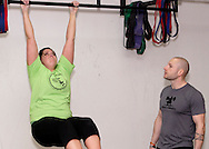 Owner Jason Hoskins of Dayton (right) watches and advises Abby Griest of West Carrollton during a workout of the day session at Vigor Crossfit in Moraine, Wednesday, January 25, 2012.