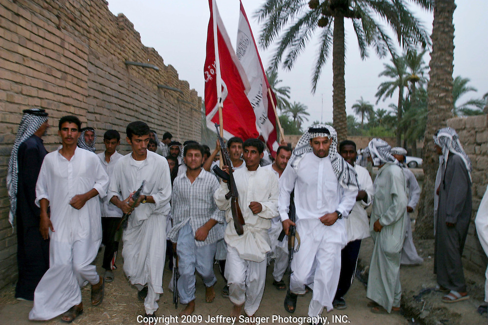 Emad Al-Kasid, at right with gun in his hand, and members of the Al Hacham Al-Kasid Tribe, red flag, merge with a neighboring tribe in their home village Suq ash Shuyukh, about 20 miles southeast of Nasiriyah, Iraq, Wednesday, July 30, 2003. The men were paying respects to a member of another tribe who was electrocuted Tuesday night. The man was a guest at the Istikbal, or homecoming celebration, for Malik Al-Kasid's family Tuesday. This was the first time Emad went to a tribal function as an official representative of the tribal council...The celebration lasts three days with different tribal chiefs, family members and friends coming and going. The Al-Kasid family fled Iraq after the Gulf War and their part in the uprising against Saddam Hussein in 1991, spent 3 years in Rafha, Saudi Arabia and finally settled in Dearborn, MI. The family hasn't been home to Iraq in 13 years.