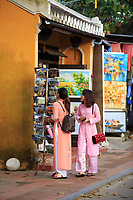 Two women in traditional Ao Dai clothing shopping on the streets of Hoi An, Vietnam