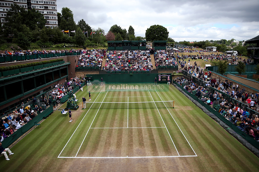 Spectators gather on court eighteen at the start of day nine of the Wimbledon Championships at The All England Lawn Tennis and Croquet Club, Wimbledon.