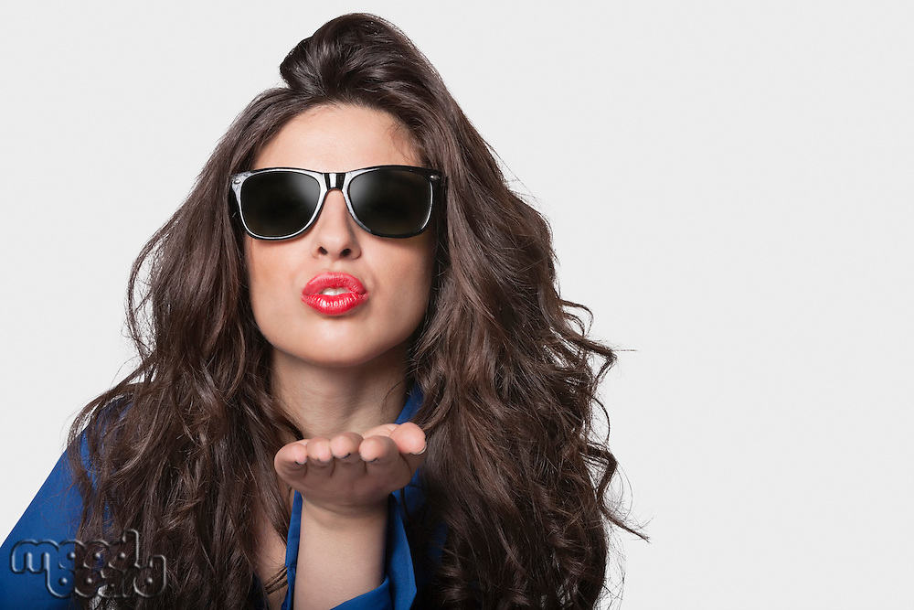 Portrait of a young woman in sunglasses blowing a kiss over gray background