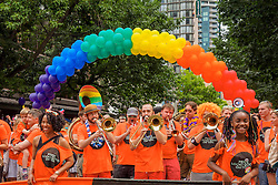 United States, Washington, Seattle Gay Pride Parade, June 28th, 2015. Contingent of Nordstrom employees and families, and rainbow arch made of balloons.