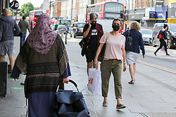 © Licensed to London News Pictures. 14/07/2020. London, UK. A shopper with a shopping a bag, and wearing a face covering, in Wood Green shopping centre in north London. From 24 July, shoppers will be required to wear face coverings during shopping. Shoppers who fail to comply with the new government rule risk £100 fines. Photo credit: Dinendra Haria/LNP