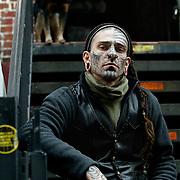Manhattan New York 26 december 2003 26-03-2003.Tattoo kunstenaar zit/ poseert op trap voor zijn tattoo pisrcing studio in Greenwich Village New York City  .Tattoo piercing artist sitting/ posing on stairs in front of his tattoo shop in Greenwich Village New York City  .Foto David Rozing/