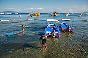 Dive shop staff load boats in preperation for  a dive in Puerto Galera, the Philippines. There are more than 45 dive sites dotted around the small island, inclusing wrecks and a UNESCO protected site know to contain 60 percent of the world's marine life.
