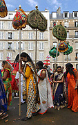 Women carrying colourful fabric banners in the parade celebrating the festival of Ganesh Chaturthi, marking the birth of the Hindu god Ganesha, on the streets of the La Chapelle area of the 18th arrondissement of Paris, France, on Sunday 1st September 2019. The annual religious festivities and parade take place near the Ganesha Temple of Paris, or Sri Manicka Vinayakar Alayam Temple, the largest Hindu temple in France. Ganesha is the elephant-headed Hindu God of Beginnings, son of Shiva and Parvati, who represents love and knowledge. Picture by Manuel Cohen