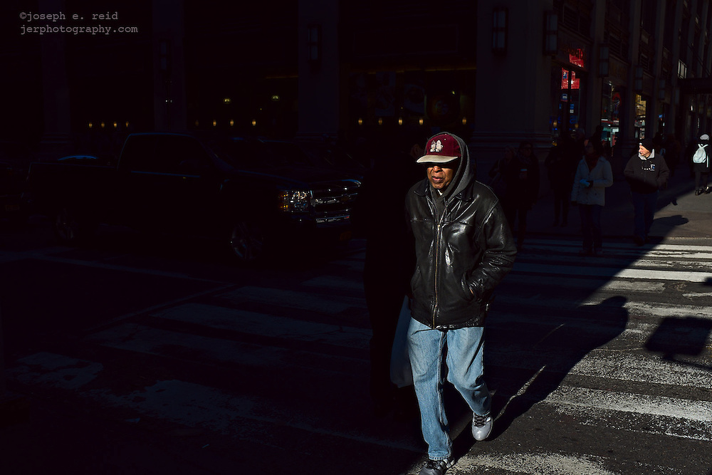 Man in red hat and leather jacket crossing street, New York, NY, US