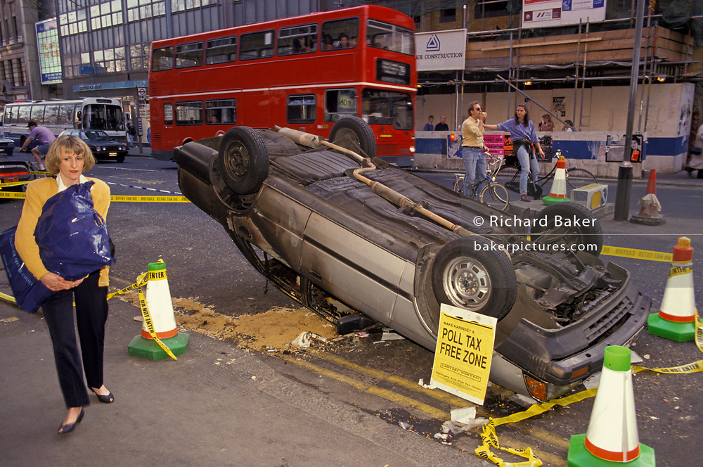 A pedestrian walks past an upturned car, a casualty of the Poll Tax riot, on 1st April 1990, in Charing Cross Road, London, England. when angry crowds, demonstrating against Margaret Thatcher's local authority tax, stormed the Whitehall area and then London's West End, setting fire to a construction site and cars, looting stores up Charing Cross Road and St Martin's Lane, on 1st April 1990, in London, England. The anti-poll tax rally in central London erupted into the worst riots seen in the city for a century. Forty-five police officers were among the 113 people injured as well as 20 police horses. 340 people were arrested.