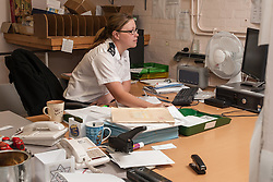 Female Prison Officer in the office, UK prison