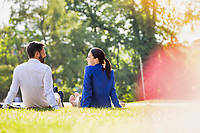 Young attractive businessman and businesswoman sitting on the grass while talking during break